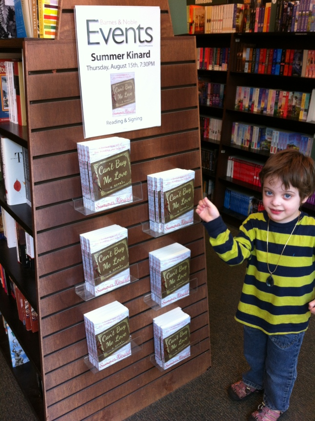 "My adorable son Pip pointing out my books on display at Barnes and Noble! ""Can't Buy Me Love?  What does that mean anyway?"" Hint: the heroine is a freegan."