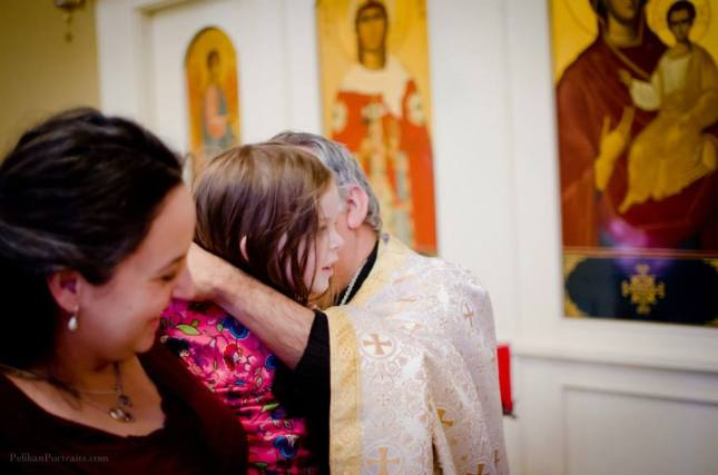 My daughter receiving her blessed cross necklace at our family's chrismation. Photo credit: Elina Pelikan