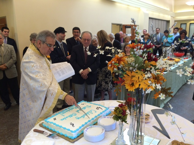 Here, the priest carves the sign of the cross into the surface of the cake.